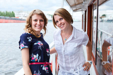 Happy women standing on ship deck during sea cruise photo