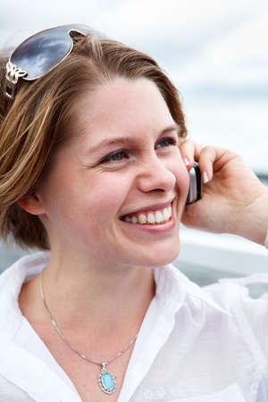Happy woman in white shirt with sunglasses calling on mobile phone  Close up photo