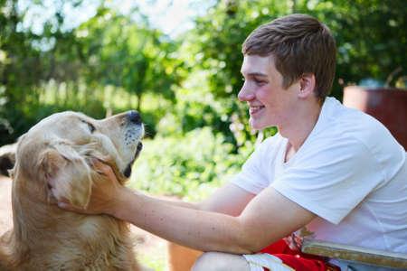 dog on leash: Adolescente, joven y feliz con el perro retriver de oro en conjunto que abarca Foto de archivo