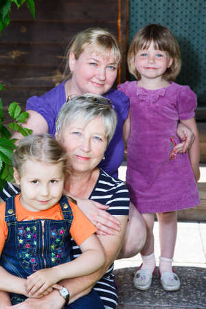 grandddaughter: Three generation female family with four people on house porch