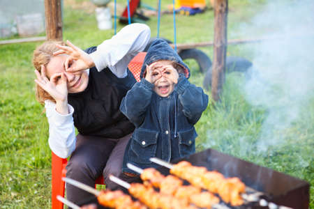 Mother and little daughter making faces during cooking meat photo