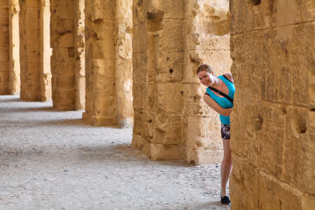 amphitheater: Young woman looking from column in demolished ancient walls and arches in Tunisian Amphitheater in El Djem, Tunisia
