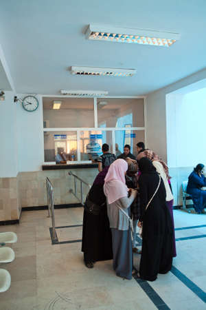 SOUSSE, TUNISIA - CIRCA MAY, 2012: Women in national clothes standing near ticket office and buying passes
