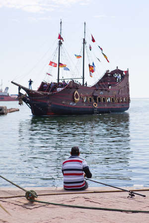 fishman:  SOUSSE, TUNISIA - CIRCA MAY, 2012: Fisher sitting on Sousse city pier. Excursion, stylized of old ship on circa May, 2012 in Sousse, Tunisia.