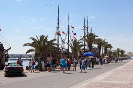 SOUSSE, TUNISIA - CIRCA MAY, 2012: Quay with walking tourists and old stylized ships in the port of city on circa May, 2012 in Sousse, Tunisia. Stock Photo - 16284617