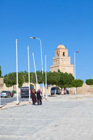 going places: KAIROUAN, TUNISIA - CIRCA MAY, 2012: Arabian people going to the Great Mosque, on circa May, 2012 in Kairouan, Tunisia. Editorial
