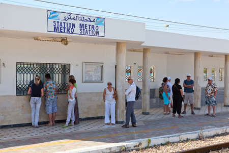 MONASTIR, TUNISIA - CIRCA MAY, 2012: Tourists stand in railway Habib Bourguiba Airport station and waiting intercity train arrival, on circa May, 2012 in Monastir, Tunisia. Stock Photo - 15583649