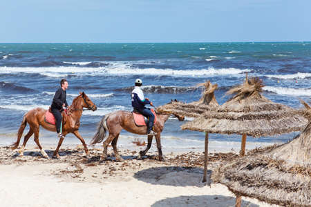 TUNIS, TUNISIA - CIRCA MAY, 2012: People on horses riding on sea waterfront. Sandy beach in Tunisia. Tourists riding for money, on circa May, 2012 in Tunis, Tunisia.