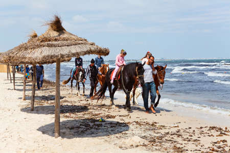TUNIS, TUNISIA - CIRCA MAY, 2012: Tourists riding for money on horses on sea waterfront. Sandy beach on circa May, 2012 in Tunis, Tunisia.