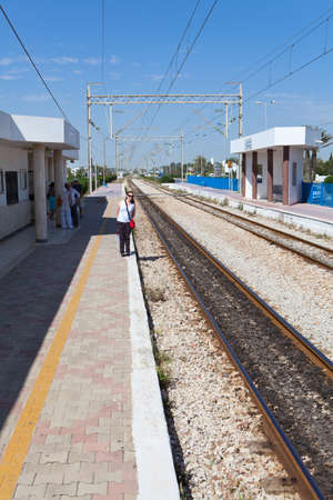 MONASTIR, TUNISIA - CIRCA MAY, 2012: Tourists stand in railway Habib Bourguiba Airport station and waiting intercity train arrival, on circa May, 2012 in Monastir, Tunisia. Stock Photo - 14685709