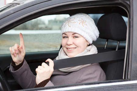 vehicle seat: Young woman sitting in car with seat belt and forefinger is up