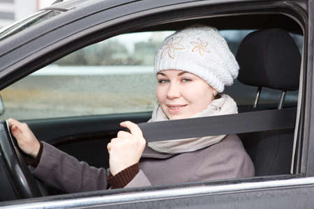 fastened: Fastened young woman sitting in car and holding seat belt in hand