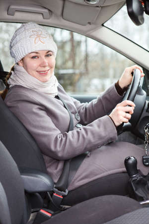 Woman in winter clothes driving a car photo