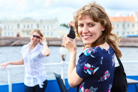 Female photographer turning back with hand-held camera photo