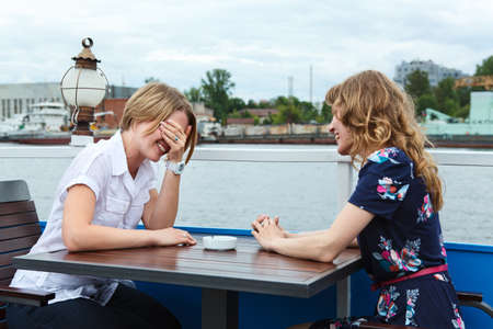 two people only: Two girlfriends talking each other at cafe table outdoors