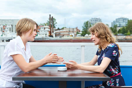 two people only: Girlfriends discussing at cafe table outdoors