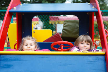 Two happy playful girls sitting in car toy on playground photo