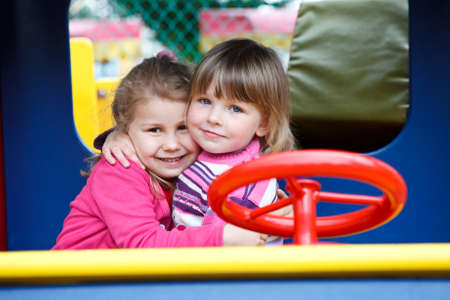 Two happy little girls embracing on playgroung at summer day photo