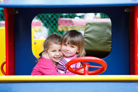 Two happy little girls embracing together on playground photo