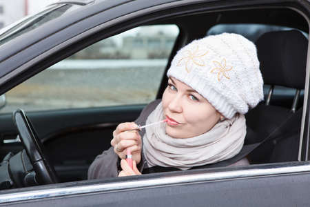 fastens: Caucasian female does make up in car, fastens seat belt