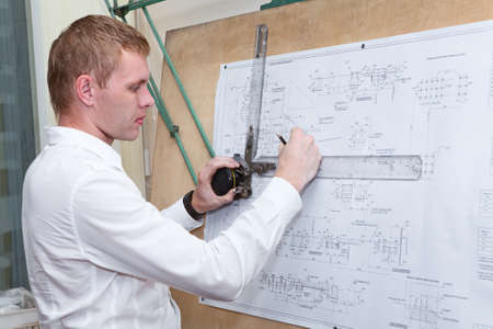 Engineer making a blueprint project with old-fashioned drawing board photo