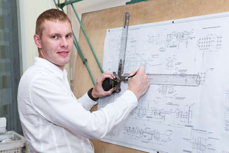 Designer making construction project by pencil on drawing board photo