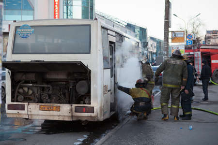 SAINT-PETERSBURG, RUSSIA - CIRCA MARCH, 2012: Passenger minibus in fire on city street and firefighters extinguish, on circa March, 2012 in Saint-Petersburg, Russia