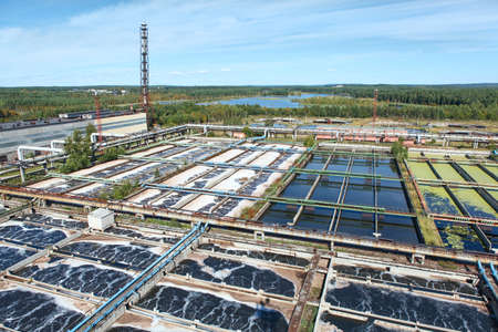 riool: Luchtfoto van waterzuiveringsinstallatie in naaldbossen Redactioneel