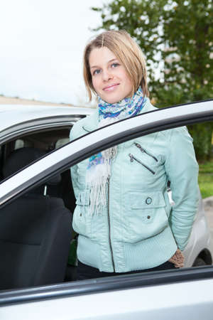 Young pretty woman standing bear a car with opened door photo