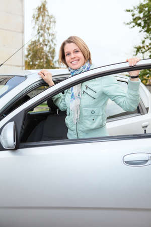 Young pretty woman standing behind a car with opened door photo