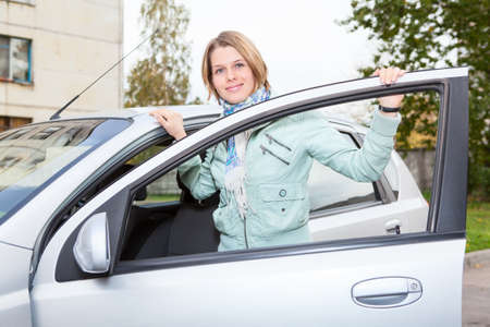 Young pretty Caucasain woman standing behind a car with opened door photo