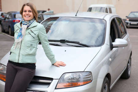 Young pretty Caucasain woman standing behind a new own car photo
