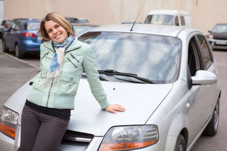 Young Caucasain woman standing behind a new own car photo
