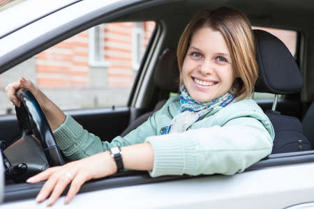 Female driver sitting in car, smiling and holding steering wheel photo
