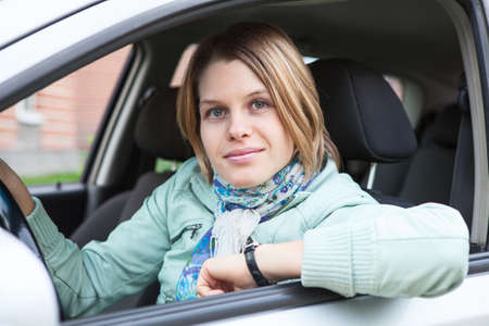 Joyful blond hair woman sitting in land vehicle and looking at camera photo