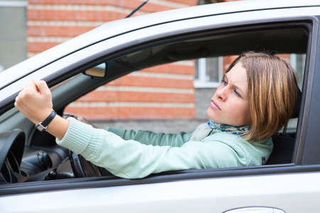 Young blond woman shaking hers fist sitting in car
