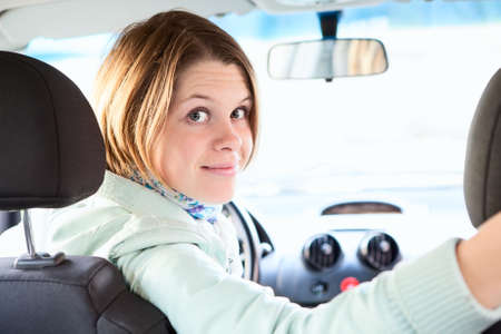 Joyful woman inside of car looking back from driver seat photo