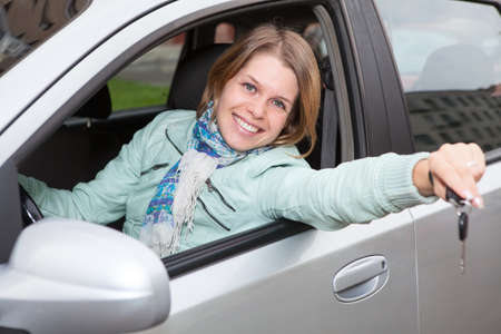 Happy smiling blond with ignition key showing in car window photo