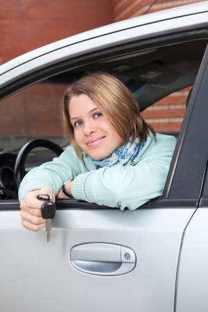 Happy woman in car window with ignition key photo
