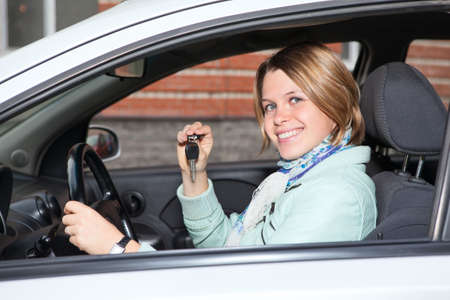 Portrait of female driver with car key in hand