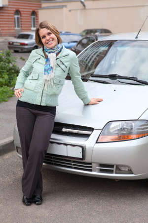 Happy beautiful woman standing in front of own new car photo