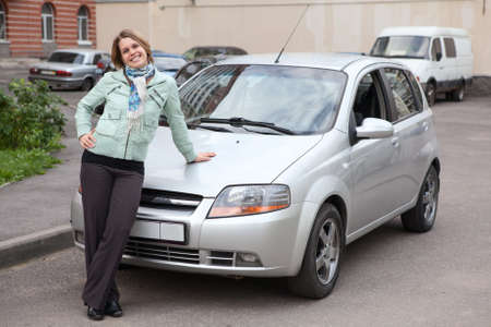 new car: Happy woman standing in front of own new car Stock Photo