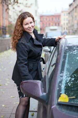 Happy Caucasian woman holding car door handle to sitting in vehicle photo