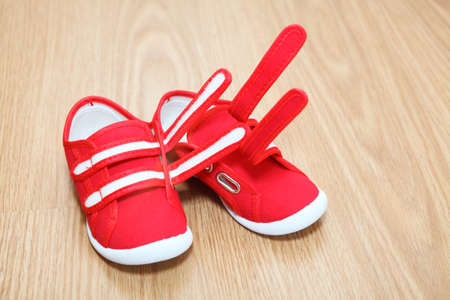 Red children shoes standing on the floor Stock Photo - 16162558