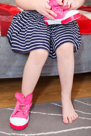 Small girl wearing pink shoes on leg sitting on sofa