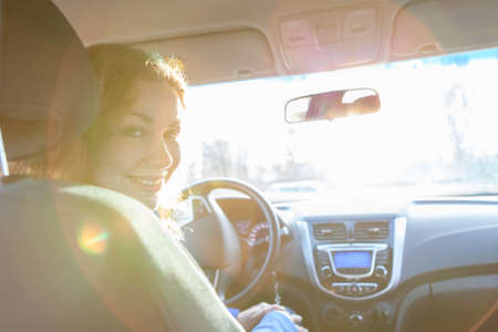 looking back: Looking back and sitting inside of car woman with sun rays in window Stock Photo