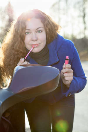 near side: Pretty woman applying make-up near car back side mirror against sunlights