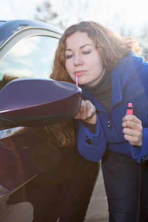 near side: Curly hair woman applying make-up near car back side mirror against sunlights