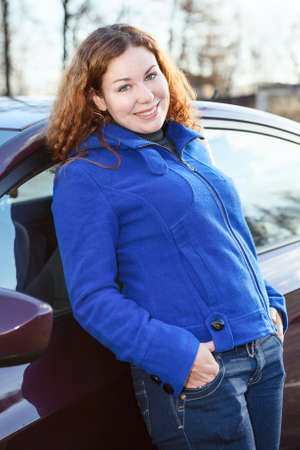 Curly hair woman standing near car and looking at camera photo