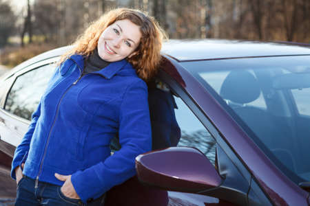 leaned: Beautiful woman leaned to car smiling and looking at camera